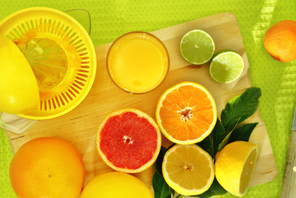 Slices of citrus fruit and a fresh juice on a wooden tray