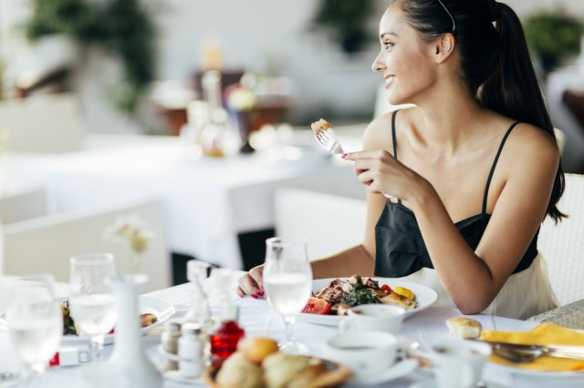 BM_Beautiful woman eating meal in restaurant_93172999